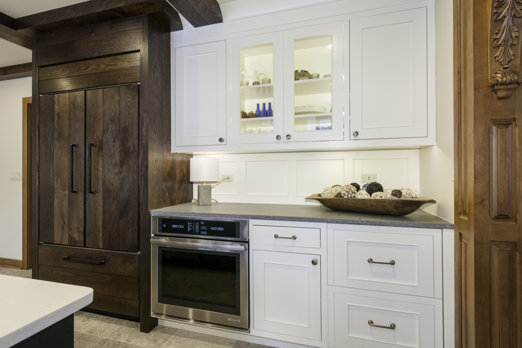 kitchen with white cabinets, oven, and wood panel refridgerator