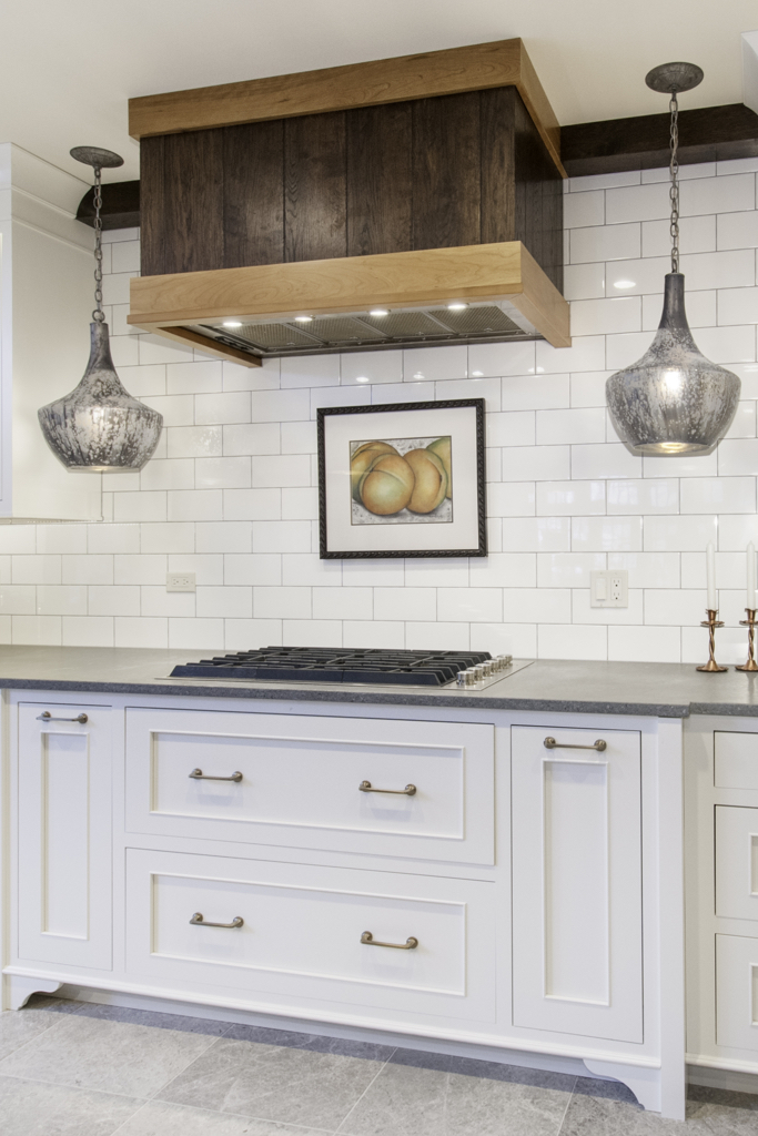 stove with white cabinets and wood stove hood