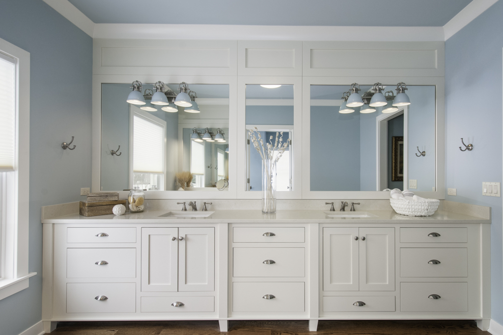 blue bathroom with white cabinets and