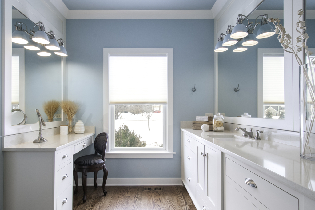 blue bathroom with white cabinets and vanity