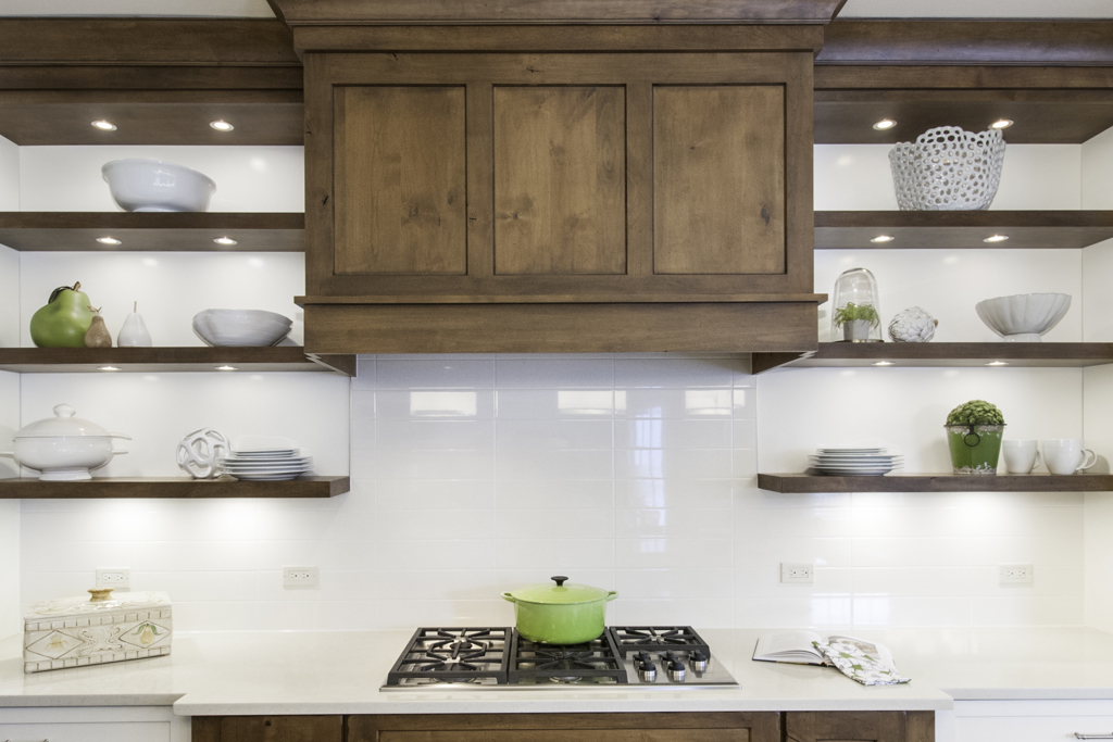 Kitchen with wood hood over stove and shelves