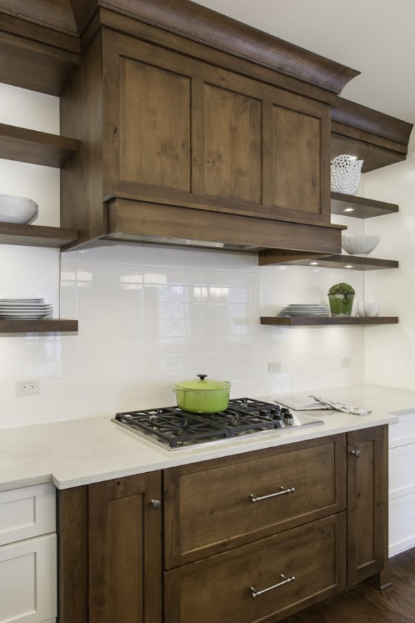 Stove with wood cabinetry, shelves, and hood